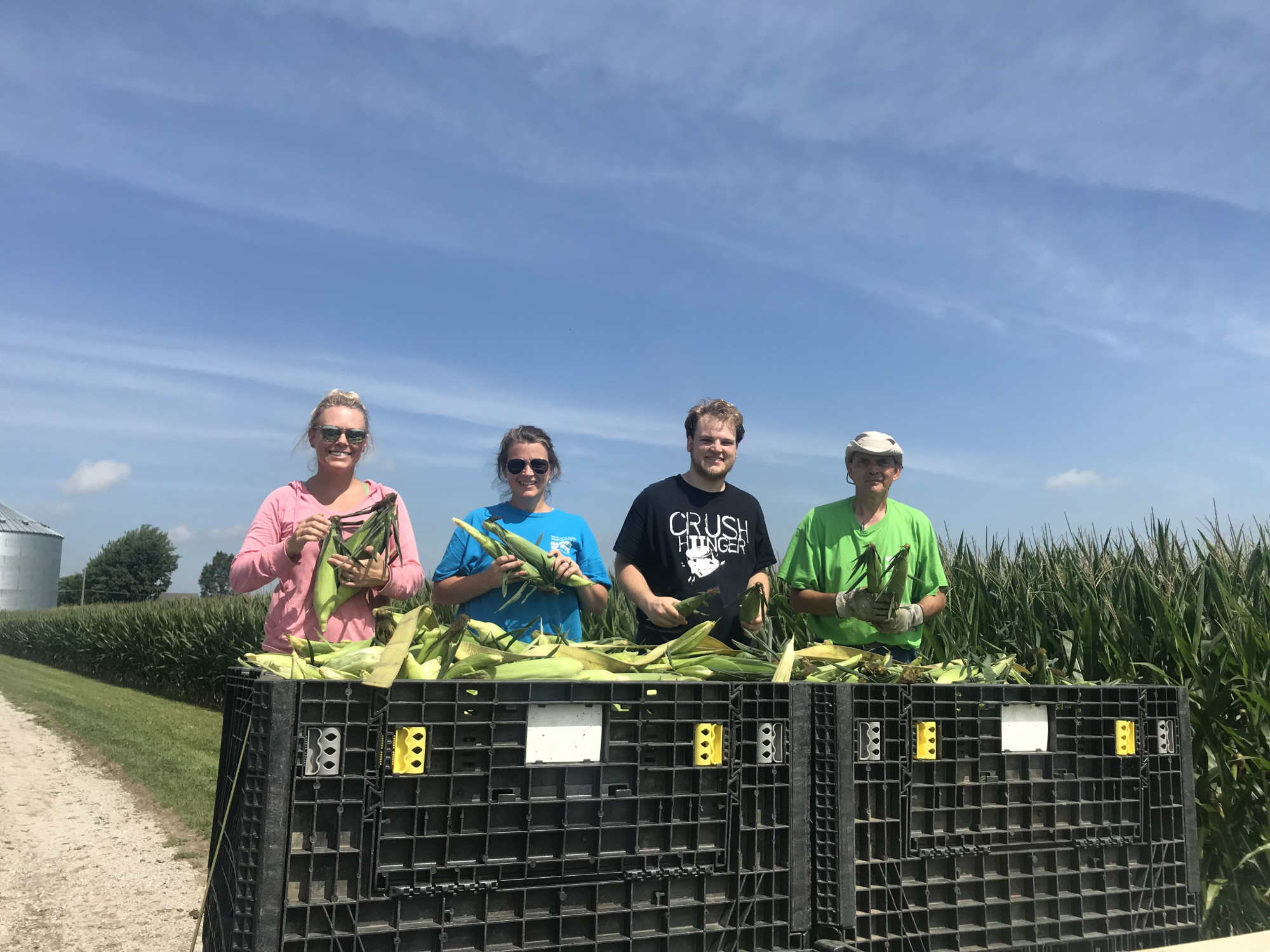 Four people stand next to a corn field holding corn that was gleaned for the Food Rescue US program.