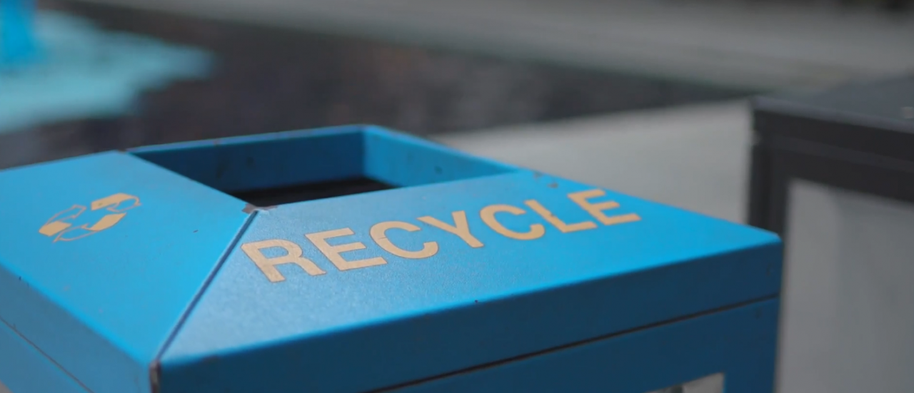 Blue recycling bin with words